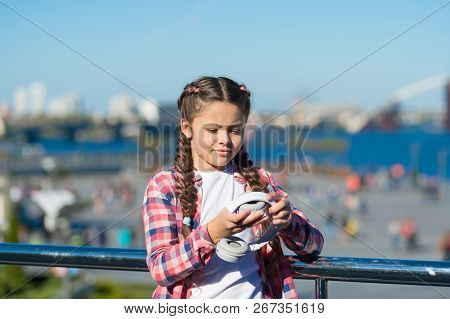 Girl Little Kid Hold Foldable Headphones While Walk Outdoors. Modern Music Gadget. Benefits Of Folda