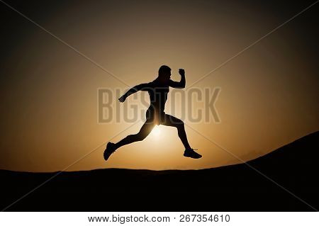 Silhouette Of Running Man On Sunset Fiery Sky Background In Mountain, Sport And Recreation, Future A