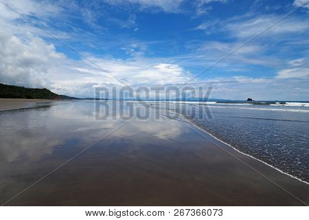 Playa Hermosa, Nicaragua At Low Tide With Brilliant White Clouds Reflected On The Exposed Beach.