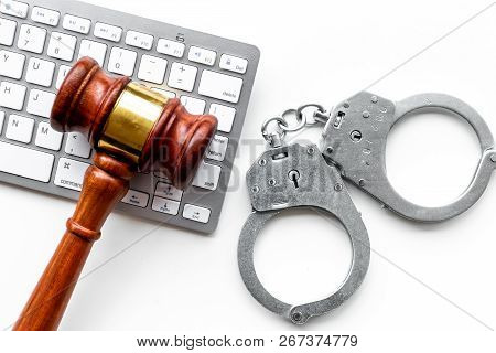 Arrest Of A Hacker For Cyber Fraud Concept. Handcuff Near Keyboard And Judge Gavel On White Backgrou