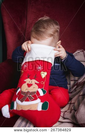 Cute Lovely Small Boy Holding A Red Christmas Stocking Sitting On The Classic Velvet Red Armchair