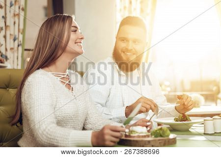 Happy Man And Woman Have Lunch In A Restaurant. A Smiling Couple Of Men And Women Are Enjoying Their
