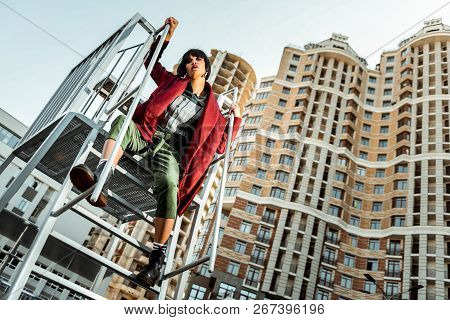 Tired Haughty Woman Carelessly Sitting On The Metal Wearing Abstract Clothes
