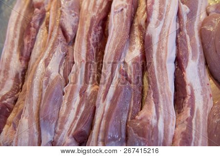 Close Up Of Cutting Streaky Pork In Fresh Market. Background And Texture Of Streaky Pork.