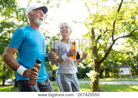 Healthy Mature Couple Jogging In A Park At Early Morning With Sunrise