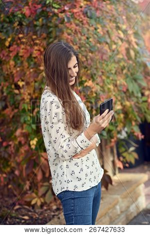 Young Woman Standing In An Autumn Street Texting On Her Mobile Phone Typing In A Message Standing Si