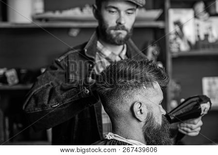 Hipster bearded client getting hairstyle. Styling concept. Barber with hairdryer drying and styling hair of client. Barber with hairdryer works on hairstyle for bearded man, barbershop background poster