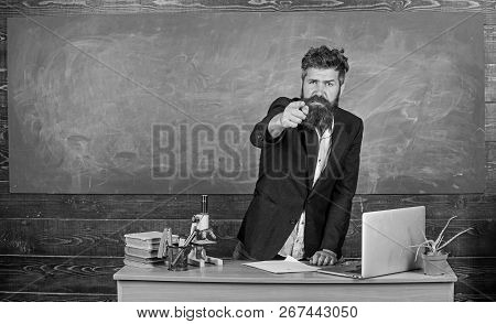Talking to students or pupils. Teacher bearded man tell interesting story. Teacher charismatic hipster stand near table classroom chalkboard background. Teacher interesting interlocutor best friend poster