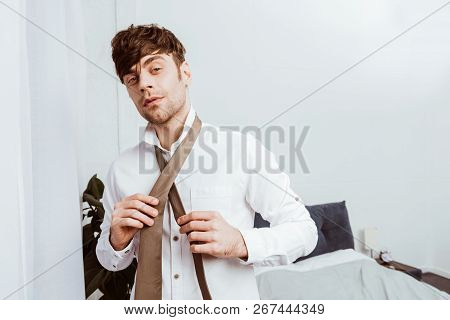 Selective Focus Of Businessman In White Shirt Tying Neck Tie At Home