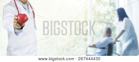 Healthy And Medical People Concept, Doctor Holding Stethoscope And Standing On Soft Blurred Nurse Ta