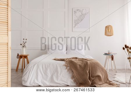 Map On The Wall Of Stylish Bedroom Interior With Big White Bed And Beige Blanket, Real Photo