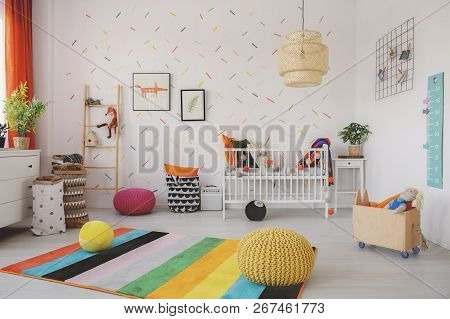 Poufs On Colorful Rug In Scandi Baby's Room Interior With Cradle And Posters On Wallpaper. Real Phot