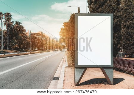 The template of an empty billboard placeholder near the highway with palms; blank urban advertising banner mockup; white empty information signboard near the road stretching into the vanishing point poster