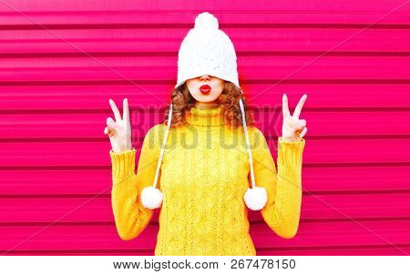 Cool Girl Blowing Red Lips Makes Air Kiss Wearing Colorful Knitted Hat, Yellow Sweater Over Pink Bac