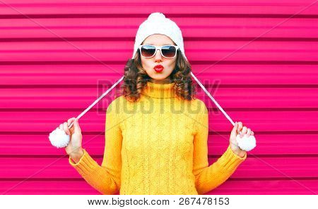 Funny Girl Blowing Red Lips Makes Air Kiss Wearing Colorful Knitted Yellow Sweater Hat Over Pink Bac