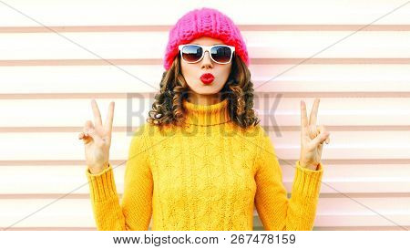 Funny Happy Girl Blowing Red Lips Makes Air Kiss Wearing Colorful Knitted Yellow Sweater Hat Over Wh