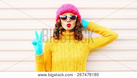 Cooll Funny Girl Blowing Red Lips Wearing Colorful Knitted Yellow Sweater Pink Hat In Gloves Over Wh