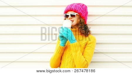 Cool Girl Drinks Coffee From Cup Wearing Knitted Colorful Pink Hat Yellow Sweater Over White Backgro