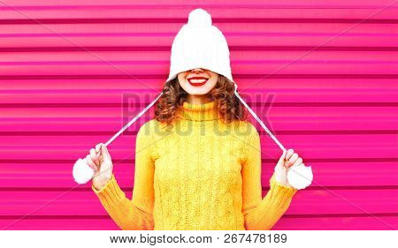 Cool Girl Wearing A Colorful Knitted Yellow Sweater Over Pink Background