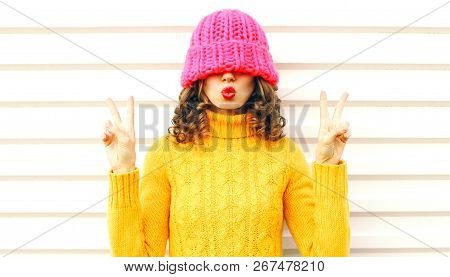 Cool Girl Blowing Red Lips Makes Air Kiss Wearing Colorful Knitted Pink Hat, Yellow Sweater Over Whi