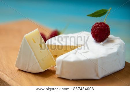 Cheese Camembert With Raspberries On A Blue Table