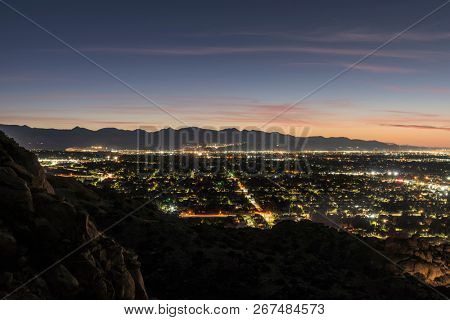Predawn rocky mountaintop view of the San Fernando Valley in Los Angeles, California.  Chatsworth, Burbank and the San Gabriel Mountains are in background.