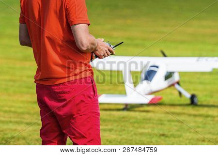 Man Flying A Model Airplane With A Controller On A Green Lawn In The Summer