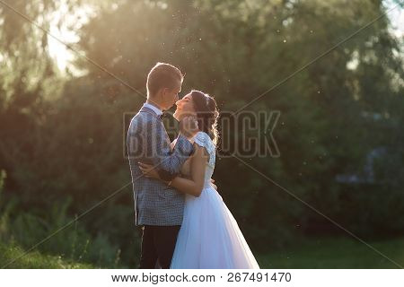 Just Married Loving Hipster Couple In Wedding Dress And Suit On Green Field In A Forest At Sunset. H