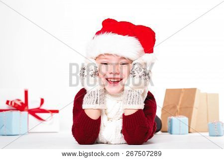 Merry Christmas And Happy New Year! Cute Happy Little Boy Holding Present. Kid Enjoy Holiday With Sa