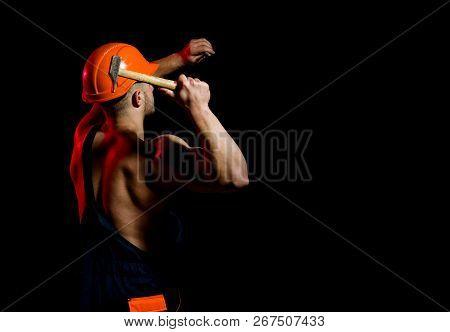 Building Under Construction. Muscular Man Builder At Work Under Construction. Man Work With Hammer.