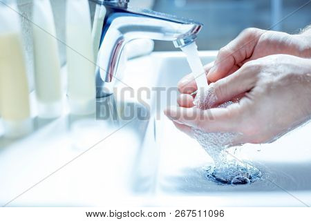 Close Up Of Male Hands Using Soap While Washing Hands In Bathroom