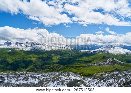 Snow on summit in the French Alps Mountains against a blue sky with white clouds