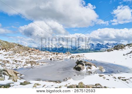 Frozen lake on summit in Alps. Mountains in France in summer