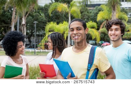 Egyptian Male Student With Other International Students Outdoors On Campus Of University In Summer