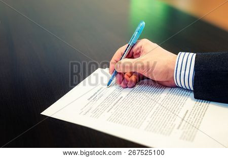 Cropped Closeup Of A Man Hand Filling In Non Disclosure Agreement (nda). Reading And Signing Busines
