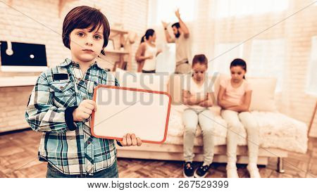 Sad Boy Showing Blank Board Family Background. Sad Little Boy Holding Paper Board For Text. Social I