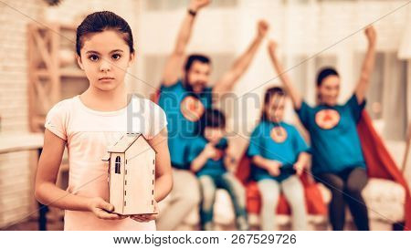 Little Sad Girl Showing Toy House Near Cute Family. Sad Little Girl Holding Toy House. Social Issue,