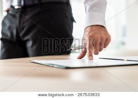 Businessman Standing Next To His Office Desk Holding A Pen Pointing On A Document Or Subscription Fo
