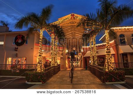 Christmas Lights Glow At Sunset Over The Colorful Shops Of The Village On Venetian Bay In Naples, Fl