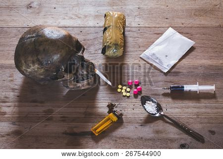 Drugs Of Various Kinds And Human Skulls On The Wooden Table, Collection Of Different Hard Drugs Hero