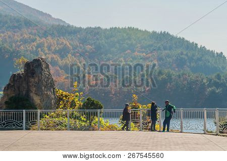Gumsan, South Korea; November 4, 2018: Three Unidentified Asians Standing At Fence Overlooking Lake