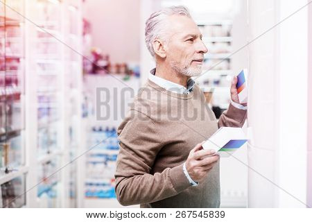 Doubting Customer Deciding Between Two Boxes In A Pharmacy