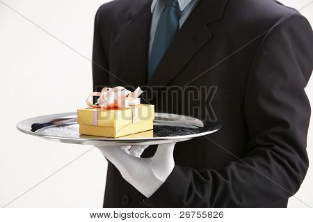 saleman holding a sliver tray with  gift