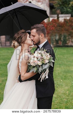 Gorgeous Bride And Stylish Groom Passionately Kissing Under Umbrella In Rainy Outdoors. Sensual Wedd
