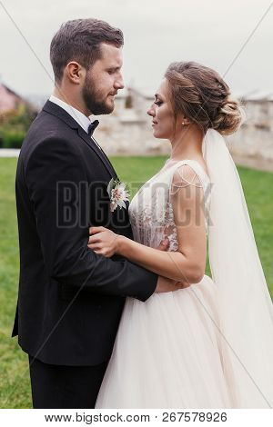 Gorgeous Bride And Stylish Groom Gently Hugging And  Posing  Outdoors. Sensual Wedding Couple Embrac
