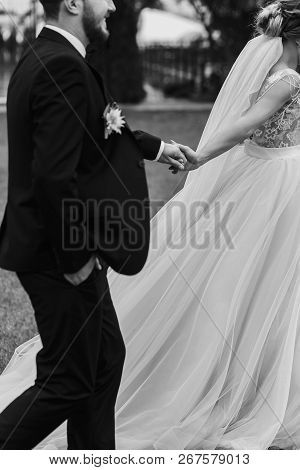 Gorgeous Bride And Stylish Groom Holding Hands And Walking Outdoors. Happy Sensual Wedding Couple Em