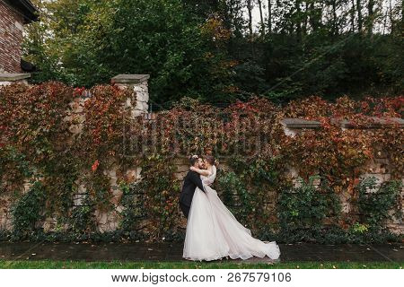 Gorgeous Bride And Stylish Groom Gently Hugging And Smiling At  Old Wall Of Autumn Red Leaves. Happy