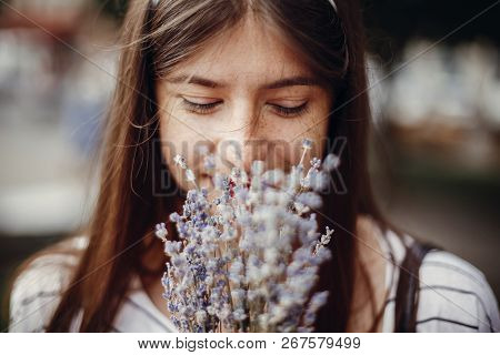 Beautiful Stylish Young Woman Holding Amazing Lavender Flowers And Smelling Them In Sunny Outdoors.