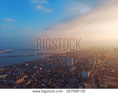 Aerial panorama of dramatic sunset above evening Voronezh city in haze or fog, bird eye view of urban downtown architecture in twilight, toned poster