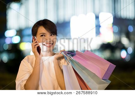 Woman Speak Phone Happily And Take Shopping Bag At Night